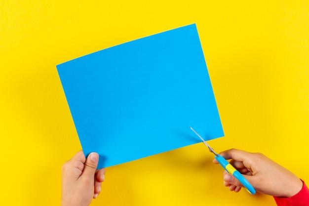 Mani del bambino che tagliano carta colorata con le forbici