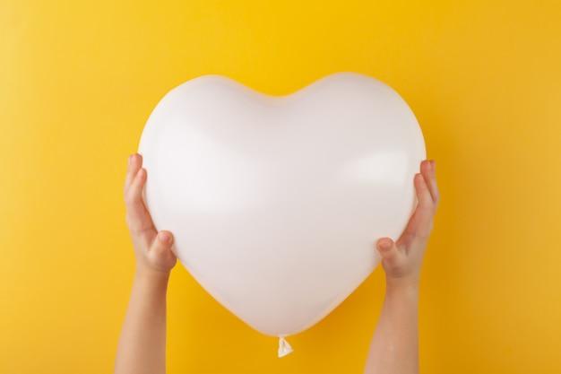 Kid mani tenendo palloncino bianco a forma di cuore, amore e il giorno di san valentino concetto, orizzontale, parete gialla, copia spazio, vista dall'alto