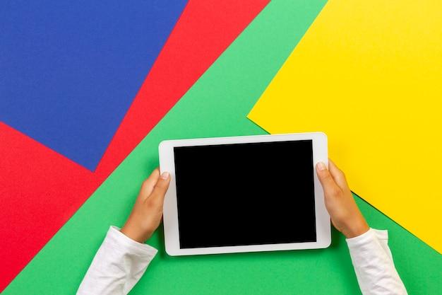 Mani del bambino che tengono il computer tablet bianco su sfondo verde chiaro, blu, giallo e rosso