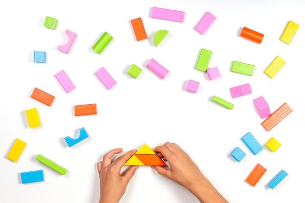 Scherzi le mani che giocano con le particelle elementari di legno variopinte sulla tavola bianca. vista dall'alto