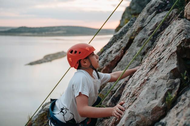 Bambino di 10 anni che scala una montagna guardando il tramonto