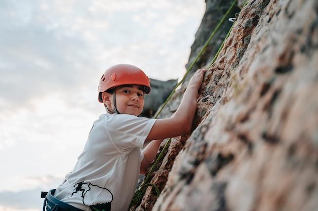 Bambino nel suo scalare una montagna mentre guarda la telecamera