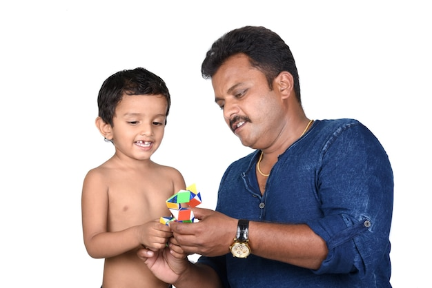 Kid e suo padre giocano con il giocattolo. ragazzo e padre del bambino giocano con il giocattolo su bianco.