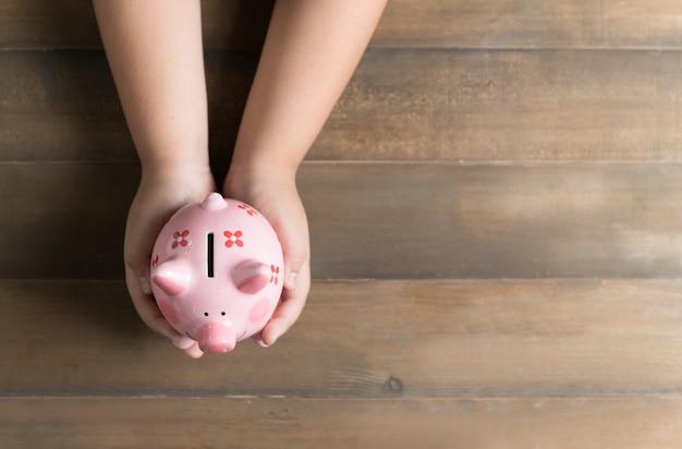 Bambino tenere una banca di maiale sullo sfondo di legno d'epoca, un risparmio di denaro per il futuro concetto di educazione e