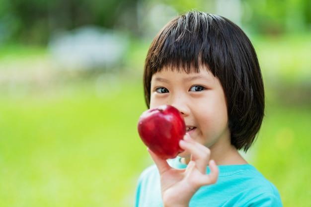 Bambino che tiene una mela con sfondo verde natura