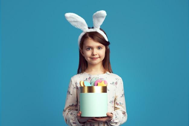 Bambino che tiene una scatola con biscotti con orecchie da coniglio e vestito carino