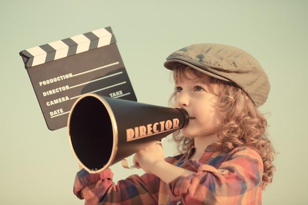 Bambino che tiene scheda di valvola contro il fondo del cielo estivo. concetto di cinema