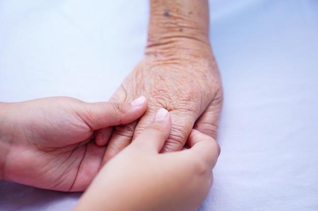 Bambino che tiene la mano paziente anziano anziana o anziana signora anziana con amore, cura e incoraggiamento.