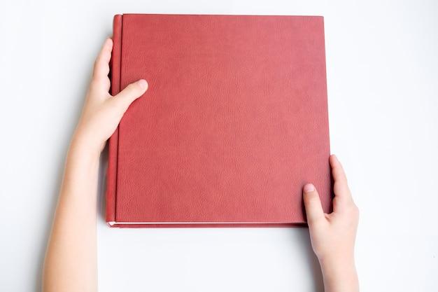 Bambino che tiene album fotografico o album rivestito in pelle rossa. photobook si trovano su sfondo bianco. vista dall'alto.