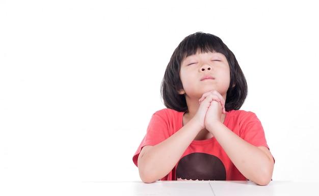 Il bambino sta pregando, le mani giunte in preghiera