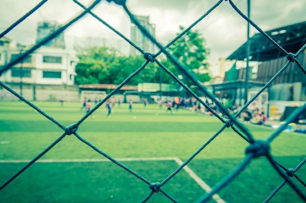 Il bambino sta allenando il calcio di calcio in sfocatura dello sfondo dietro la rete per lo sfondo e lo sfondo di allenamento sportivo di calcio e accademia di calcio