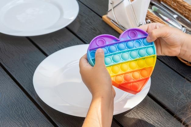 Il bambino sta aspettando il cibo in un bar fuori a giocare con un giocattolo in silicone a forma di cuore. le mani tengono un giocattolo pop it sul tavolo all'aperto.