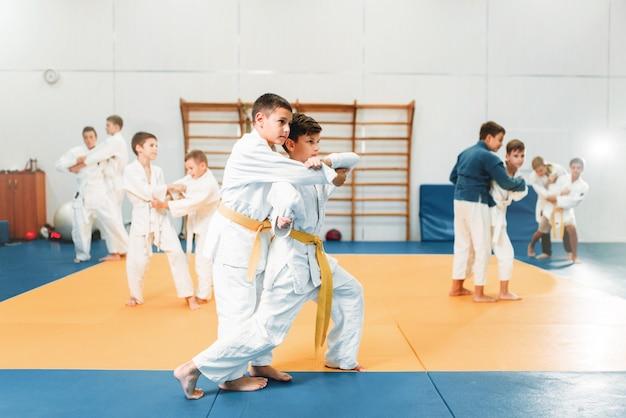 Kid judo, bambini che addestrano l'arte marziale nella hall. ragazzini in uniforme, giovani combattenti