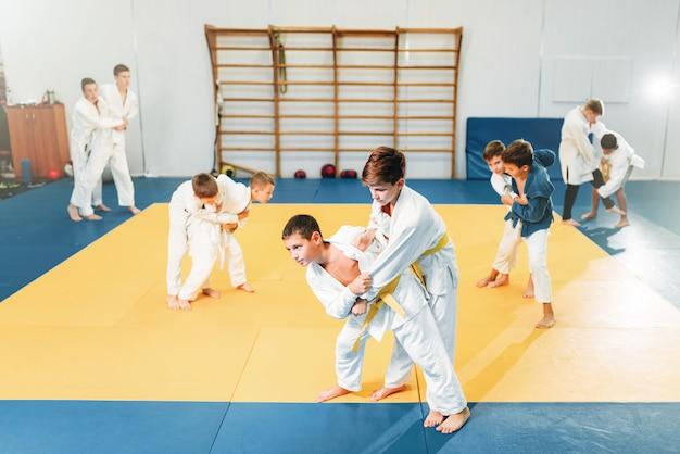 Kid judo, addestramento per bambini di arte marziale, autodifesa. ragazzini in uniforme in palestra sportiva, giovani combattenti