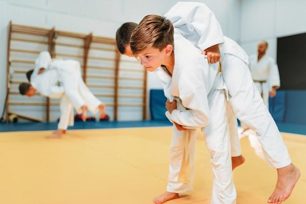 Kid judo, giovani combattenti in allenamento, autodifesa. i ragazzini in kimono praticano l'arte marziale