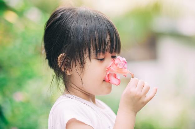 Bambino che impara il senso dell'olfatto dal fiore