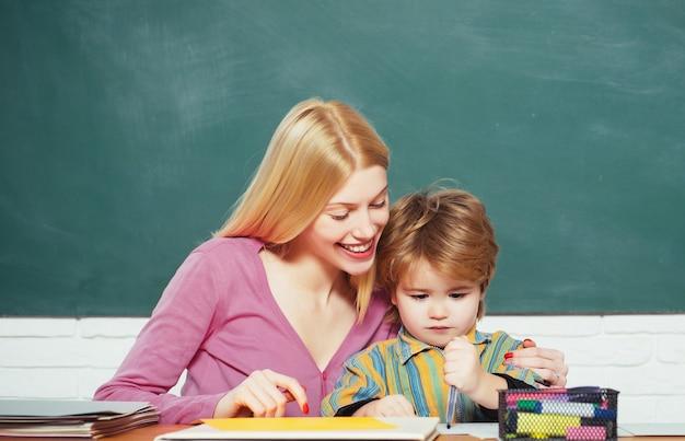 Kid ragazzino e insegnante donna pedagogo aula