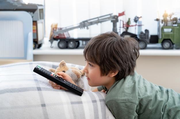 Bambino sdraiato su un cuscino che tiene il telecomando della tv con dei giocattoli sullo sfondo