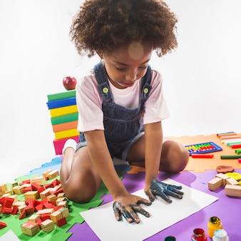 Bambino che fa handprint su carta in studio