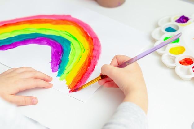 Kid pittura arcobaleno durante la quarantena