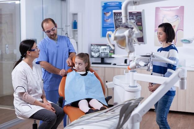 Paziente del bambino nell'ufficio del dentista preparato per il trattamento di stomatologia mentre il genitore sta parlando con il medico. bambino con sua madre durante il controllo dei denti con stomatolog seduto su una sedia.