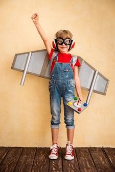 Pilota del bambino che gioca con il jetpack giocattolo a casa. successo e concetto di leader