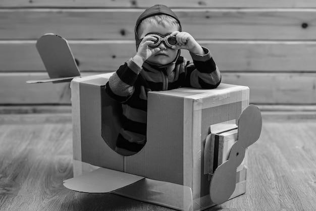 Kid, scuola pilota, innovazione. i bambini viaggiano, immaginazione. little boy bambino gioca in aereo di cartone, infanzia. consegna della posta aerea, costruzione di aeromobili. avventura da sogno.