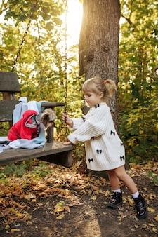 Il bambino gioca con il cane divertente sulla grande sedia di legno in giardino. bambino femminile con il cucciolo pone sul cortile. infanzia felice