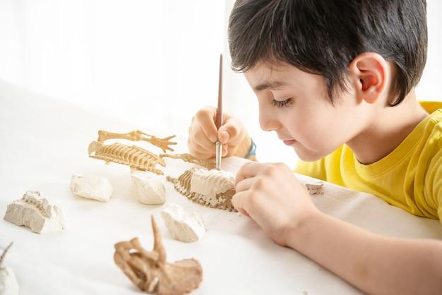 Bambino che gioca a casa da solo con un gioco di paleontologo scientifico e di precisione