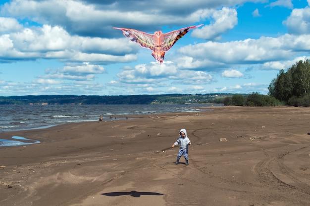 Bambino che gioca a kite sulla riva del fiume