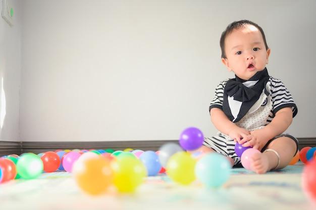Bambino che gioca con le palle sul tappeto morbido
