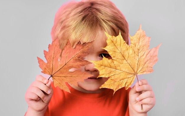 Bambino che gioca con le foglie d'acero. infanzia felice. tempo d'autunno. bambino con foglia gialla.