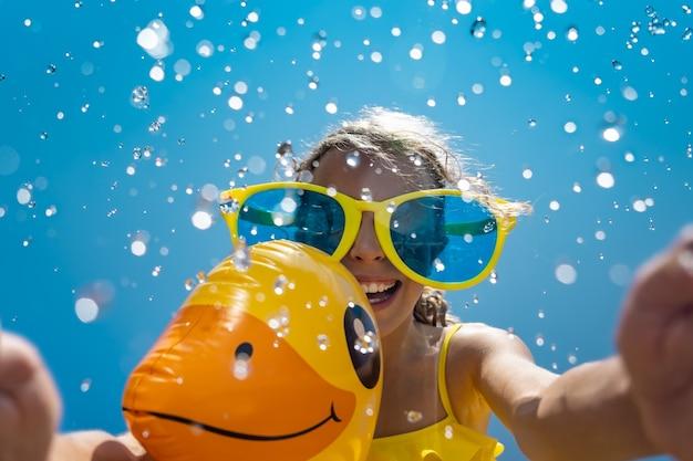 Bambino che gioca con la papera di gomma in piscina.