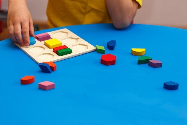 Bambino che gioca con puzzle colorato in legno, concetto di educazione