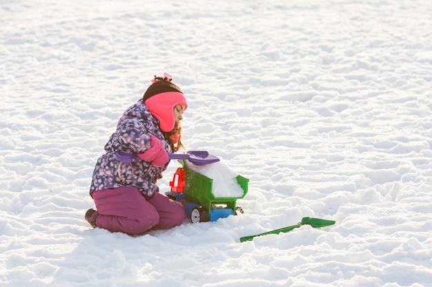 Il bambino gioca con la macchina e la pala. concetto di pulizia della neve in città