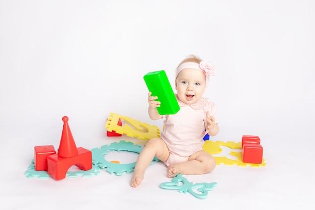 Il bambino gioca con i cubi su uno sfondo bianco isolato, spazio per il testo