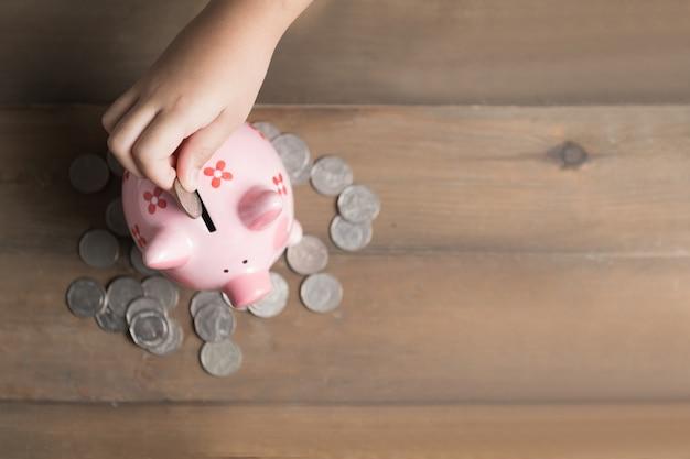 Il bambino ha messo la moneta al porcellino salvadanaio sullo sfondo di legno d'epoca, un risparmio di denaro per concep educazione futura
