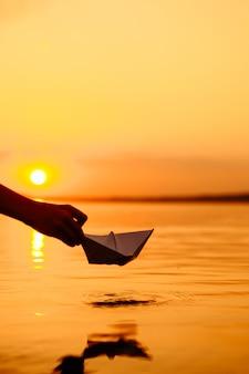 Un bambino che mette una barca di carta in acqua. tramonto bellissimo. origami. fiume. lago.