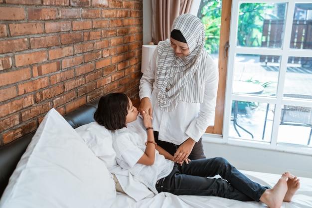 Il bambino rispetta sua madre stringendo la mano e il bacio