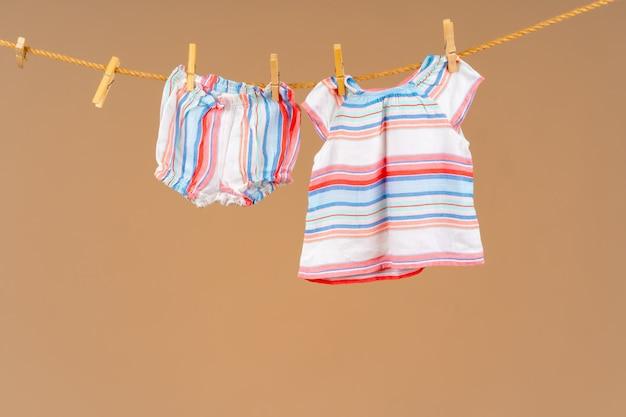 L'abbigliamento per bambini appuntato su una corda per asciugare
