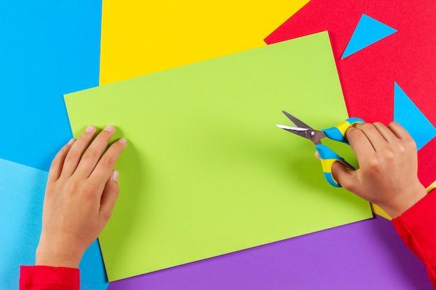 Mani del bambino che tagliano carta colorata con le forbici. vista dall'alto