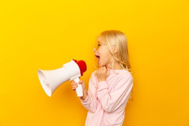 Bambino che grida tramite il megafono. concetto di comunicazione. sfondo giallo come copia spazio per il testo.