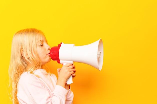 Bambino che grida tramite il megafono dell'annata. concetto di comunicazione. sfondo del cielo blu come spazio di copia per il tuo testo.