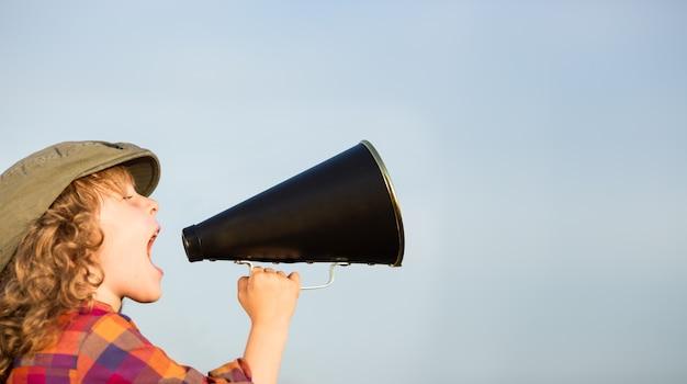 Bambino che grida attraverso il megafono vintage concetto di comunicazione sfondo del cielo blu
