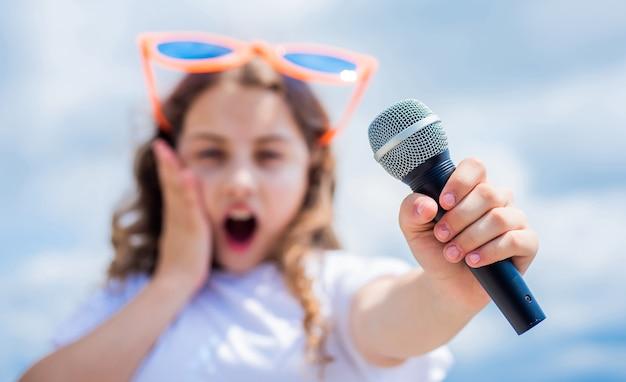 Il bambino canta con il microfono. messa a fuoco selettiva. allegro organizzatore di eventi. il bambino si diverte alla festa. cantante felice con microfono. classico fresco. ragazza che canta. concetto di scuola vocale. club di karaoke. la musica è la mia vita.
