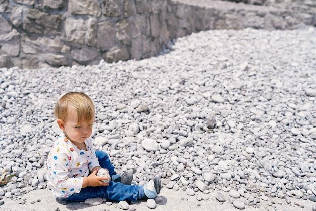 Il bambino si siede su una spiaggia di ciottoli e tiene in mano un sassolino