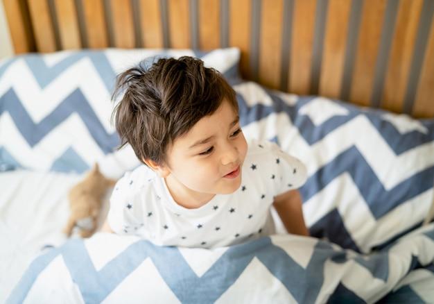 Bambino seduto sul letto a giocare con la faccia sorridente