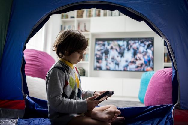 Scherzi la seduta in tenda e il gioco sul tablet