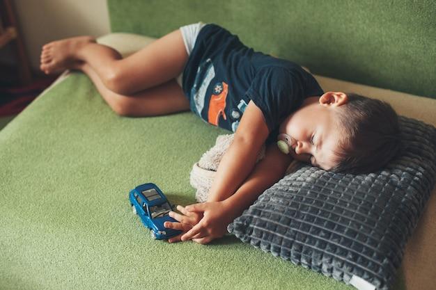 Il bambino dorme con il pisolino estivo del giocattolo dell'auto per il concetto di rilassamento dei bambini