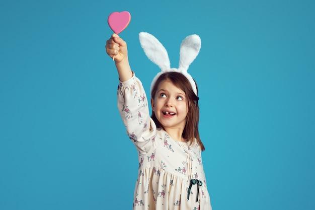 Bambino che sorride e tiene in mano un gustoso biscotto a forma di cuore dolce con orecchie da coniglio